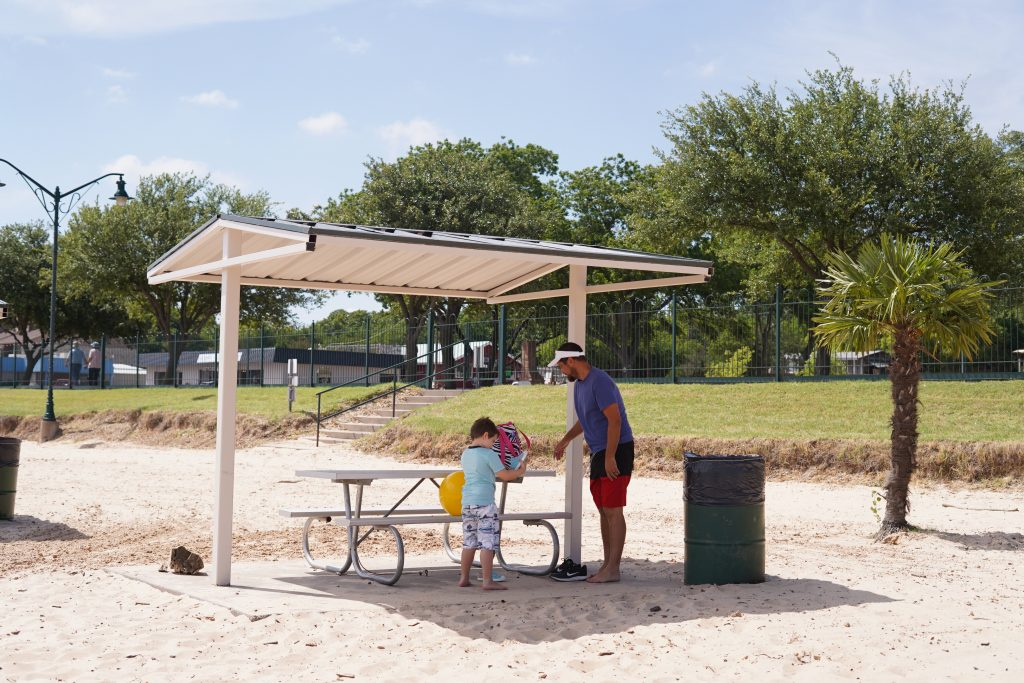 Man with little boy at the Granbury City Beach Park picnic tables.   A Guide to Granbury, Texas