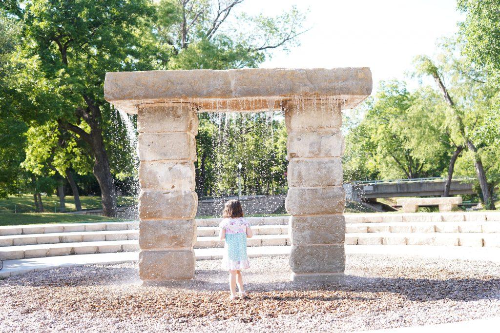 Little girl walking through water fountain at Granbury City Hall.   A Guide to Granbury, Texas