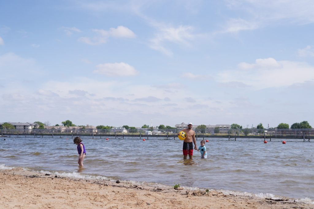 Man with kids playing and swimming in the lake.   A Guide to Granbury, Texas