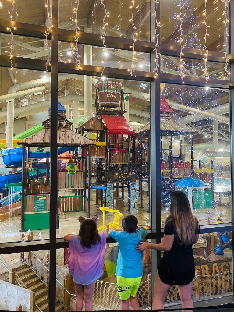 Woman with her two kids looking in the windows at the waterpark at Great Wolf Lodge.  Great Wolf Lodge in Grapevine, Texas