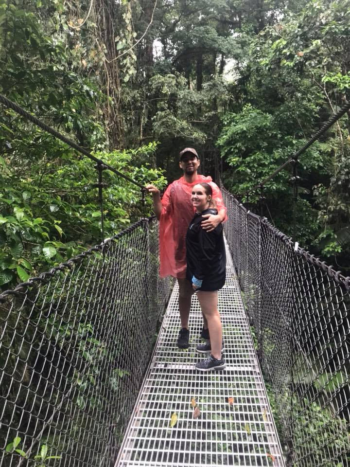 Couple standing on the hanging bridges at La Fortuna Waterfall in Costa Rica.   Costa Rica, Arenal Volcano