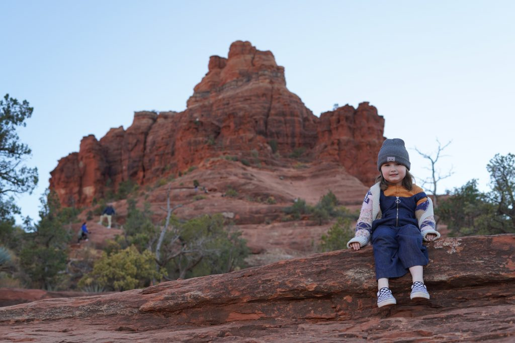 Little girl sitting on a rock ledge in Bell Rock in Sedona. | Arizona Itinerary with Kids