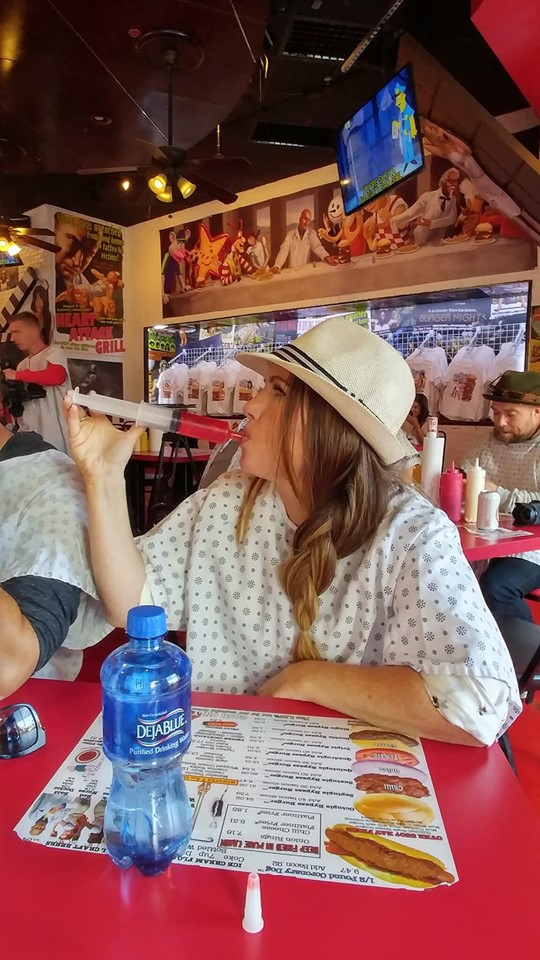 Woman taking a shot of liquor from large shot syringe at the table at Heart Attack Grill. | Las Vegas- A Guide to Vegas