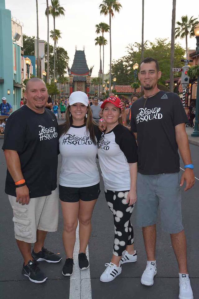Two couples posing in Disney World with matching #DisneySquad shirts.   Celebrating A Wedding Anniversary at Walt Disney World