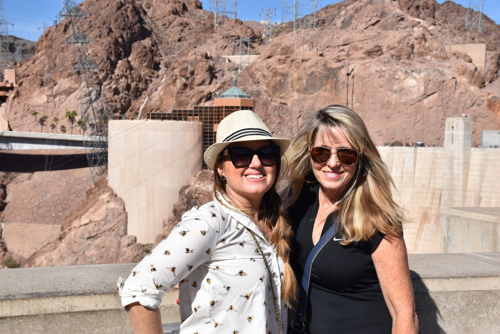 Two women posing in front of Hoover Dam.| Las Vegas- A Guide to Vegas