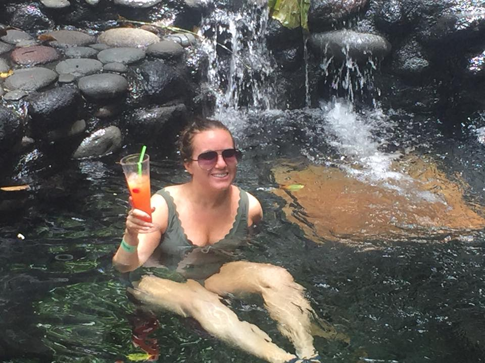 Woman in the hot springs with a cocktail at the Lava Fields Walk and Ecotermales Hot Springs in Costa Rica.   Costa Rica, Arenal Volcano