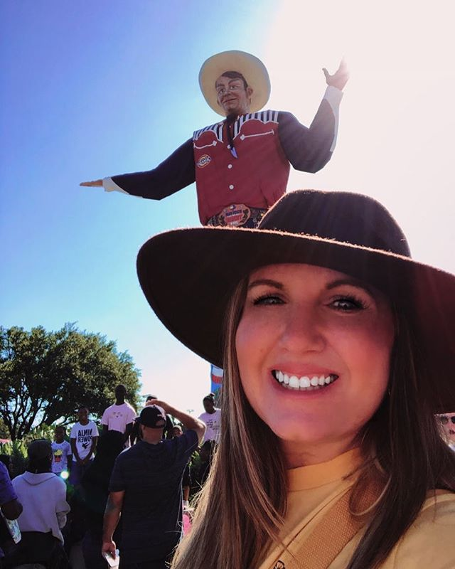 Woman taking a selfie with a giant statue of a cowboy outside.| State Fair of Texas-Dallas