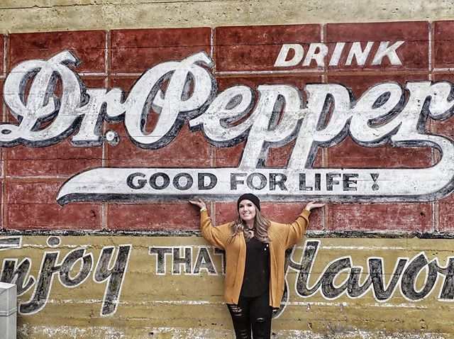 Woman posing in front of sign outside the Dr. Pepper Museum in Waco. | Waco, TX; Birthday Weekend in Magnolia