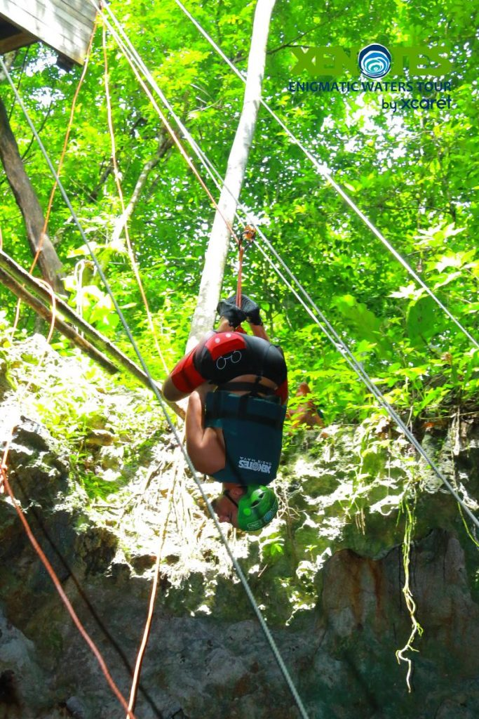 Man hanging upside down ziplining in the jungle.  A Guide to Xenotes Water Tours by Xcaret