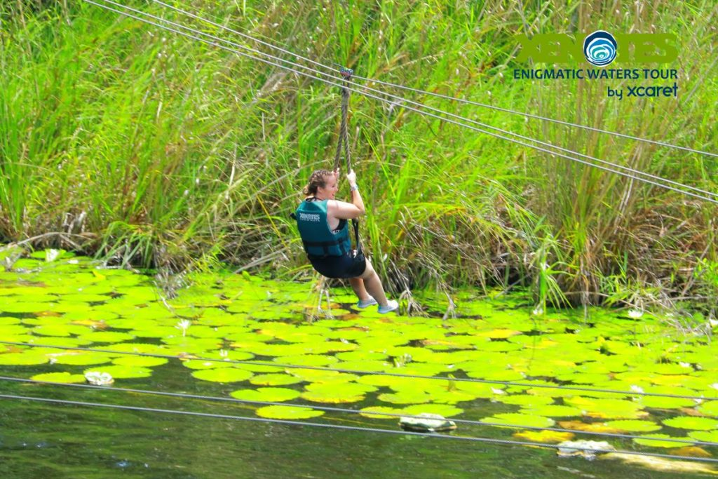 Woman ziplining over the water.  A Guide to Xenotes Water Tours by Xcaret