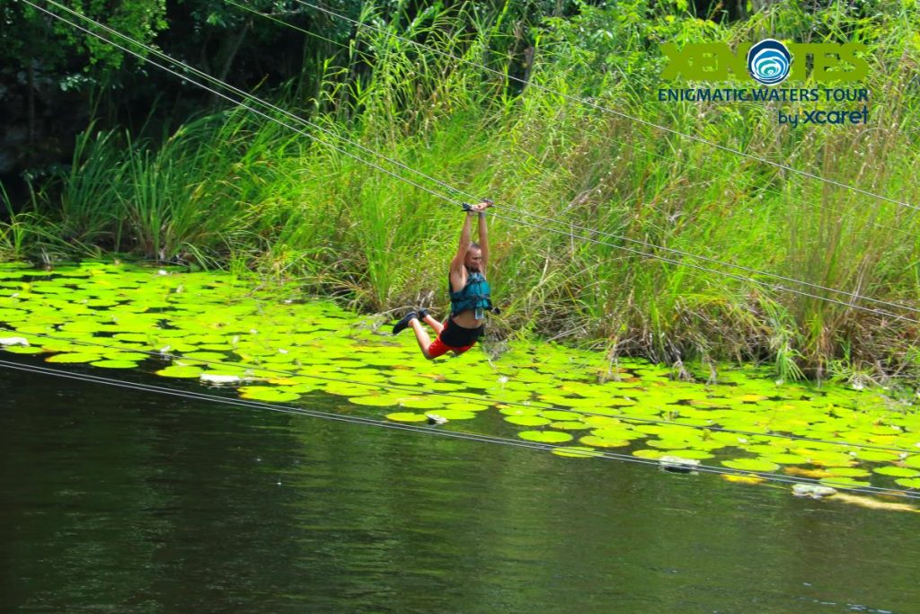 Man ziplining over the water.  A Guide to Xenotes Water Tours by Xcaret