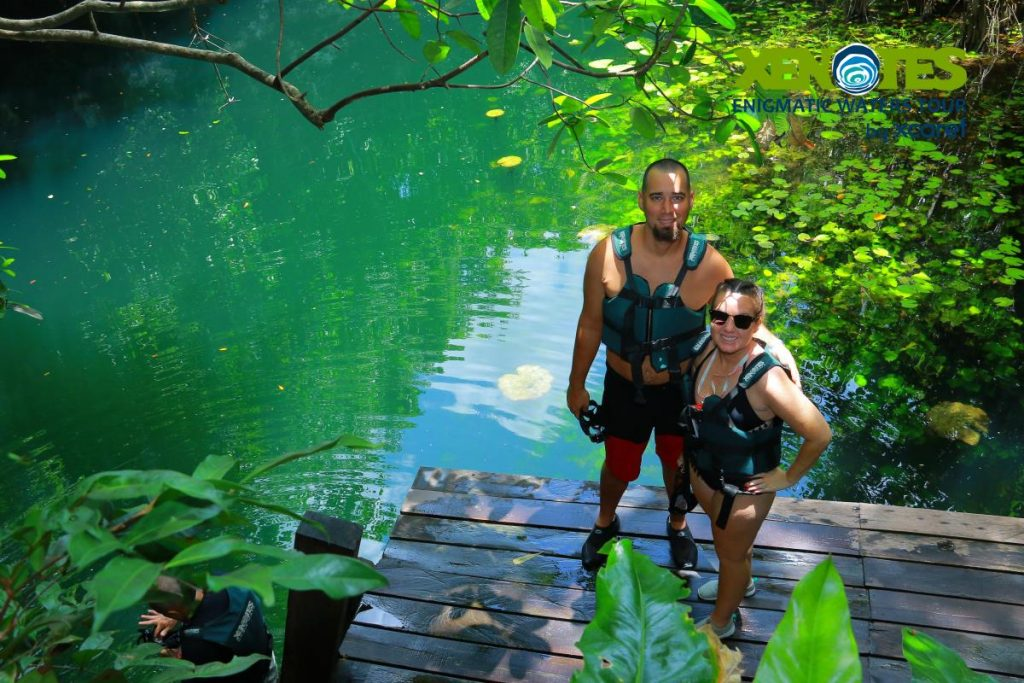 Man and woman posing on the pier with the water behind them.   A Guide to Xenotes Water Tours by Xcaret