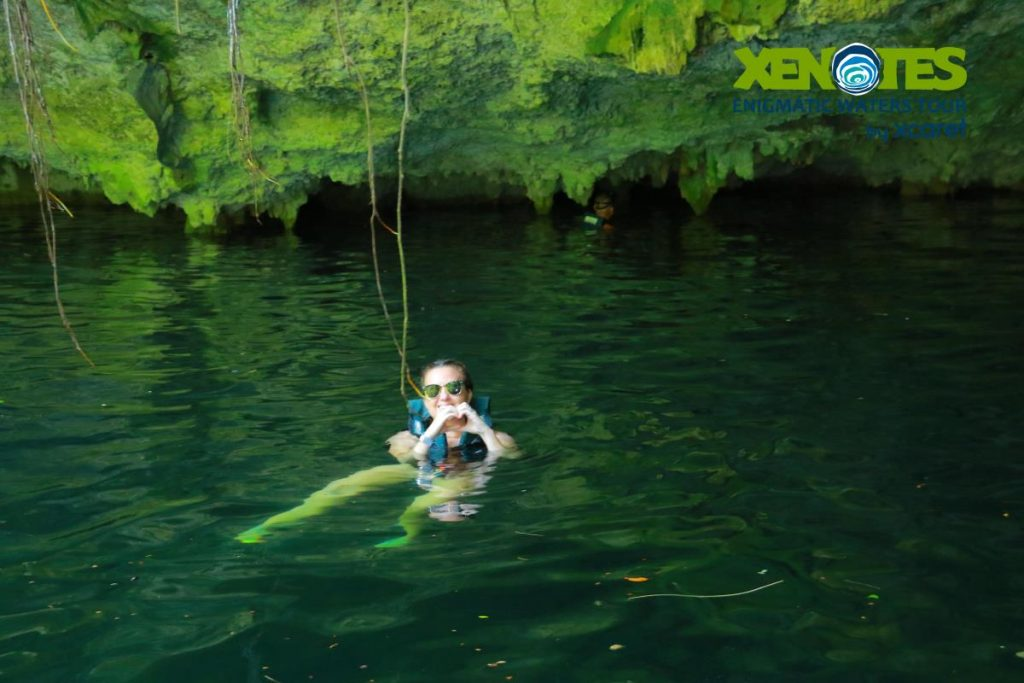 Woman swimming and posing with hands in the shape of a heart.   A Guide to Xenotes Water Tours by Xcaret
