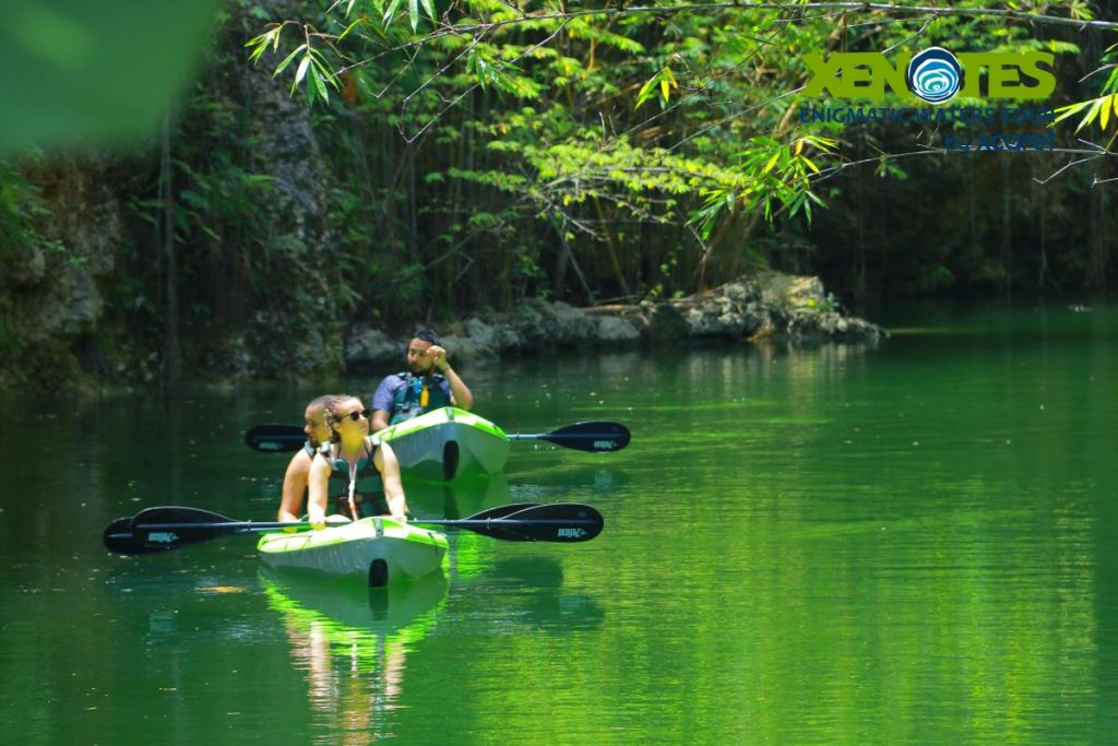 Group of people kayaking in the water.  A Guide to Xenotes Water Tours by Xcaret