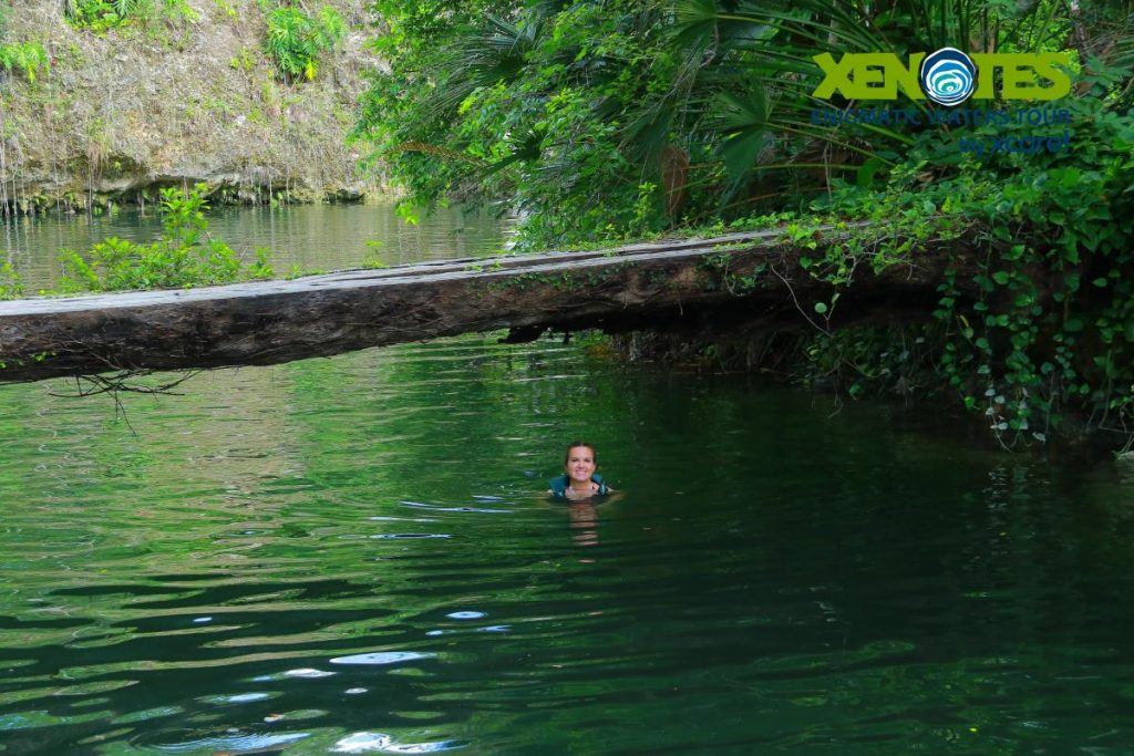 Woman swimming in the water in the jungle.   A Guide to Xenotes Water Tours by Xcaret