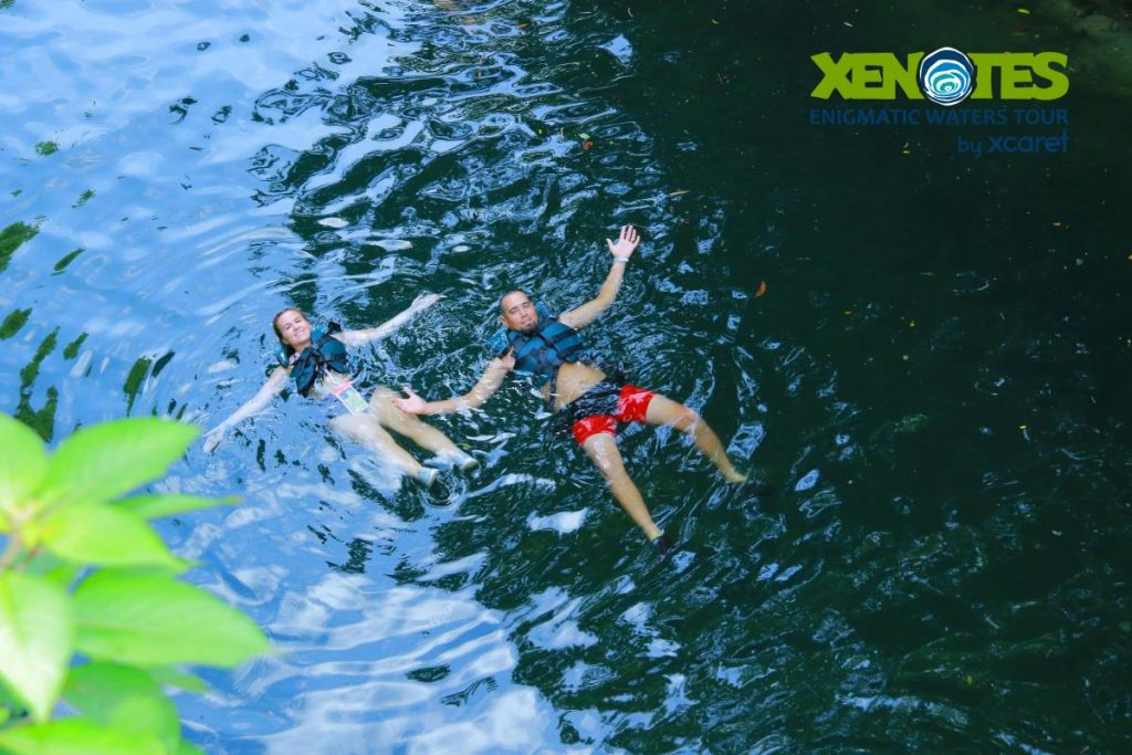 Man and woman floating in the water.   A Guide to Xenotes Water Tours by Xcaret