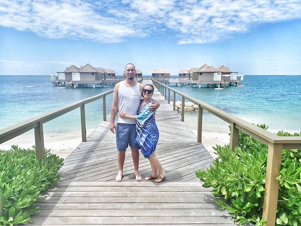 Couple posing on boardwalk with Over Water Bungalows in the background in Jamaica.   Jamaica Over-Water-Bungalows