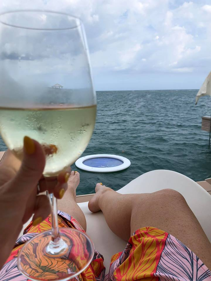 Woman drinking glass of wine at Over Water bungalow in Jamaica.   Jamaica Over-Water-Bungalows