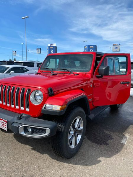 Red jeep in a parking lot.| Best Places to Visit in Colorado