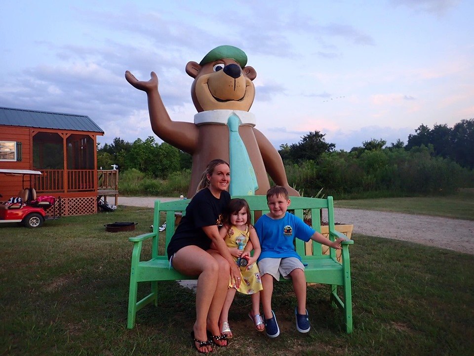 Family sitting on the bench in front of giant bear statue at Jellystone in Texas.   Jellystone Park in Waller, Texas