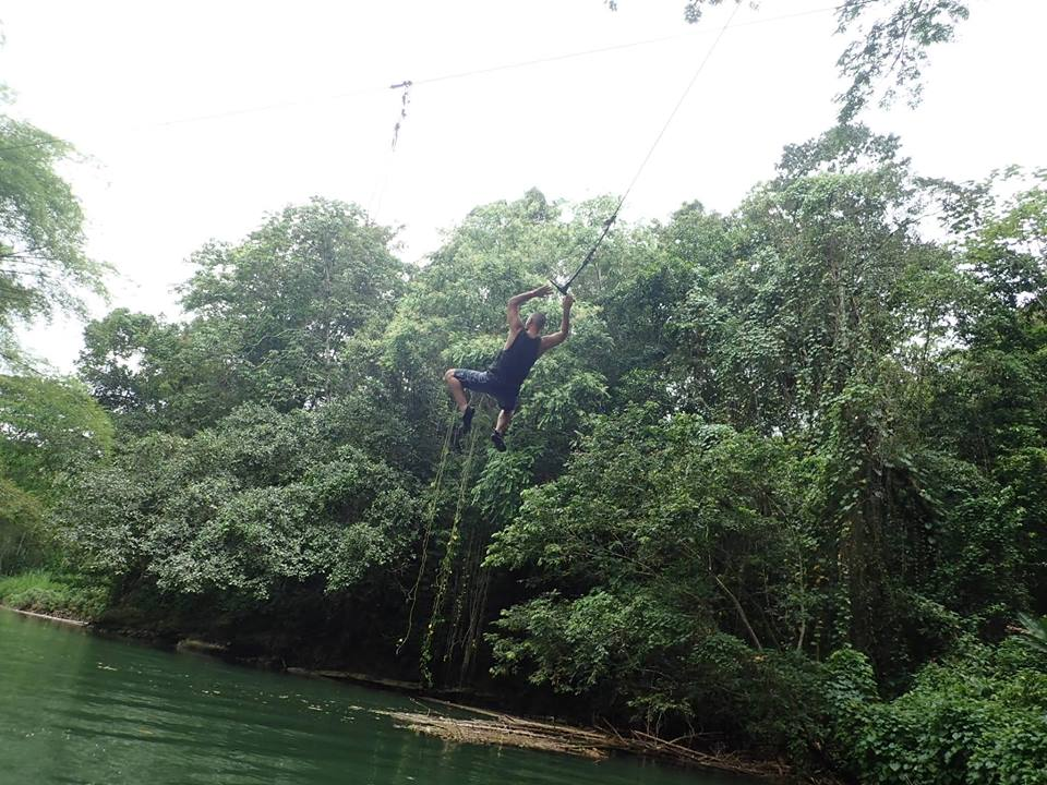 Man swinging on rope into the water the jungle at Sandals resort in Jamaica.   Jamaica Over-Water-Bungalows