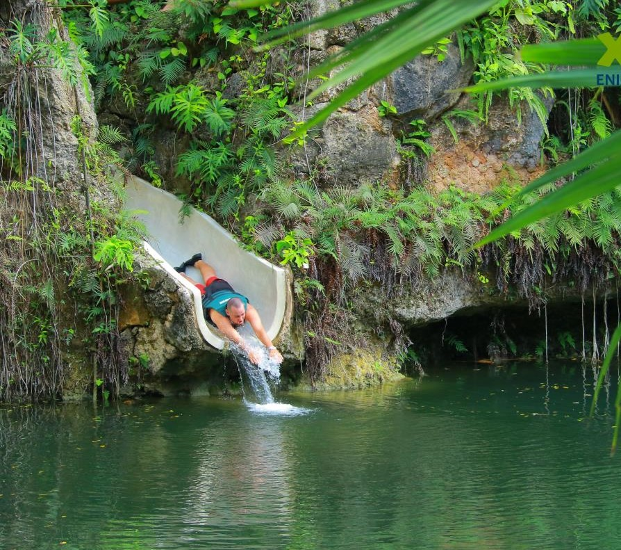 Man sliding down a waterslide into the water.  A Guide to Xenotes Water Tours by Xcaret