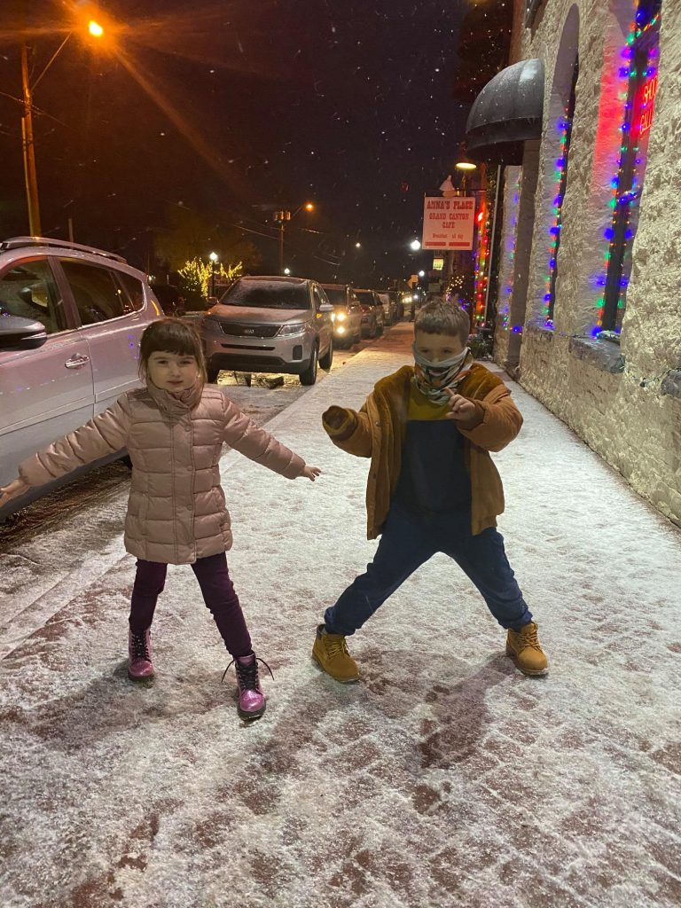 Two kids standing on the sidewalk in the snow. | Williams, Arizona on Route 66 with Kids