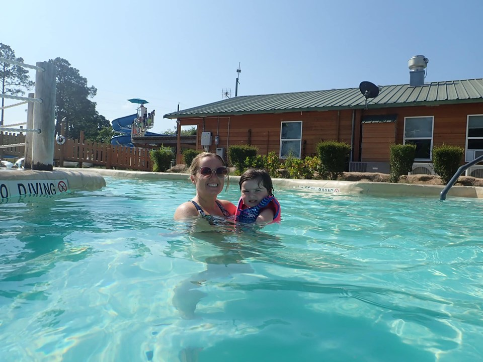 Mom and daughter swimming in the lazy river at the waterpark at Jellystone in Texas.   Jellystone Park in Waller, Texas