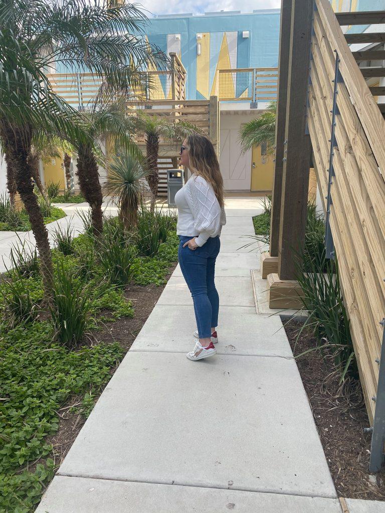 Woman walking on a sidewalk outside a hotel.| Lively Beach in Corpus Christi, Texas