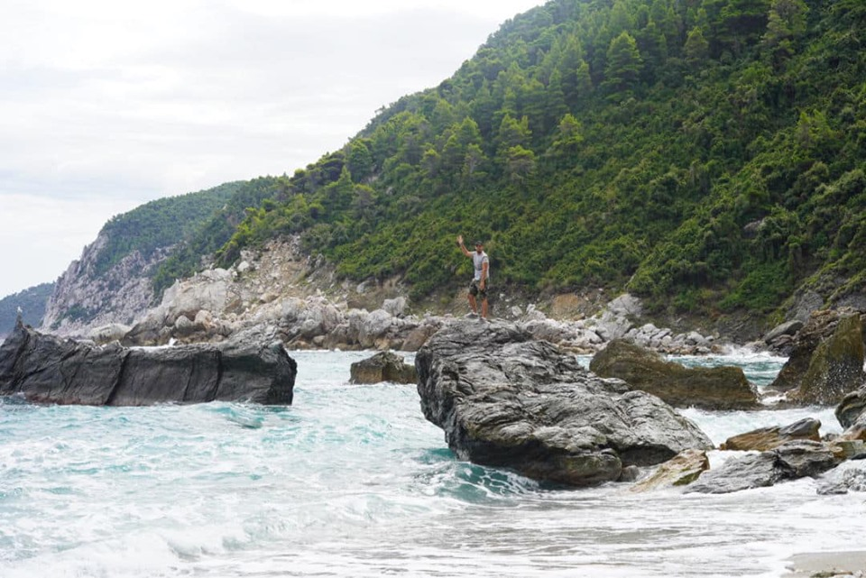 Man waving from the large rocks in the water at the Mamma Mia beach. | Skopelos Island, Greece- Mamma Mia Island