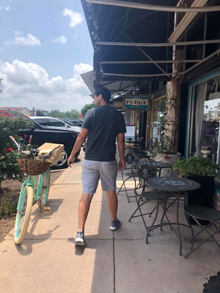 Man walking through shopping center at Marbel Falls at Cypress Valley. | Cypress Valley Canopy Tour in Austin, Texas