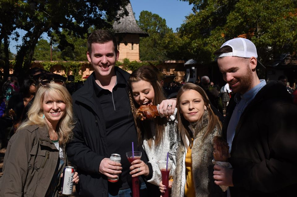 Family posing with drinks and food. | Texas Renaissance Festival
