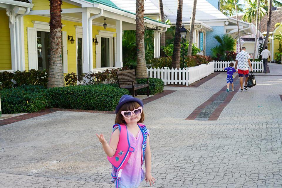 Little girl walking down the sidewalk at Marina Village at the Atlantis resort.   Atlantis, Bahamas