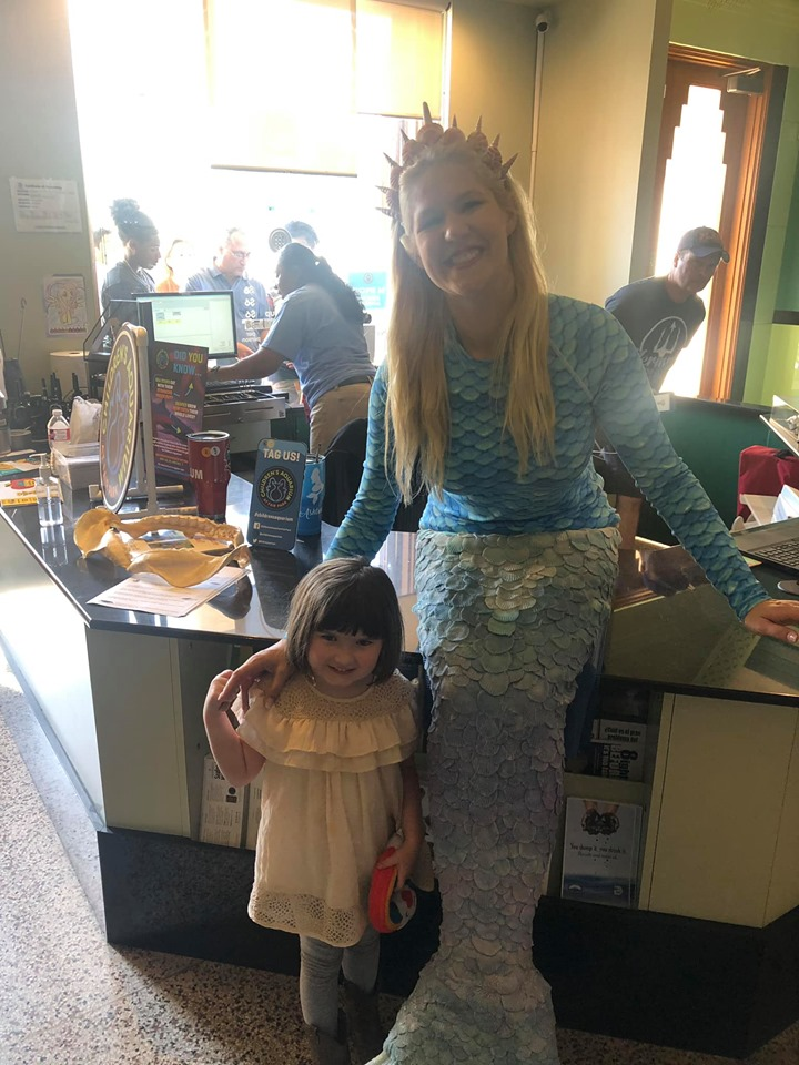 Little girl posing with a woman dressed as a mermaid at the fair. | State Fair of Texas-Dallas