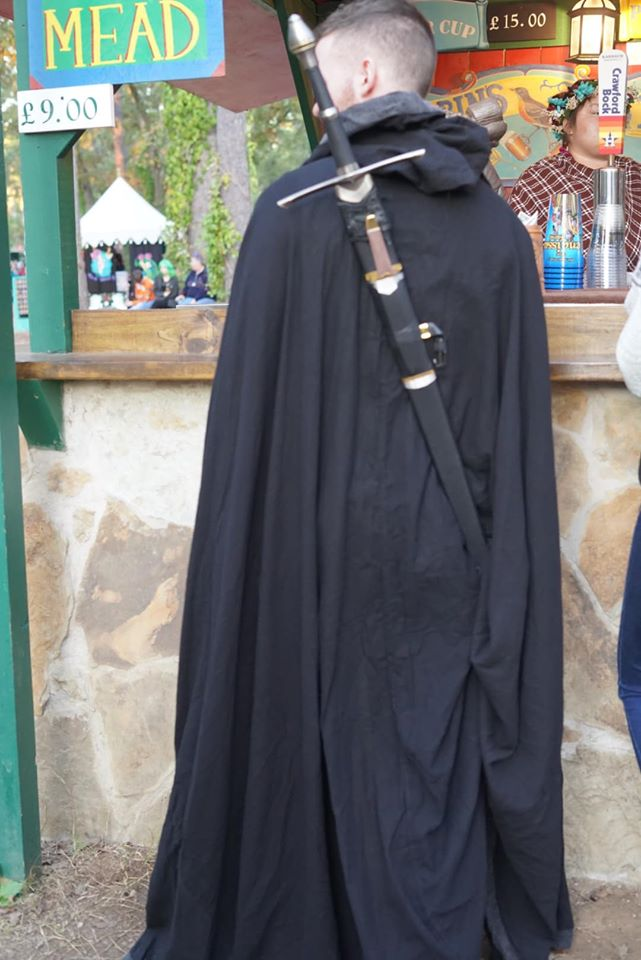 Man dressed costume with sword on back on the street.| Texas Renaissance Festival