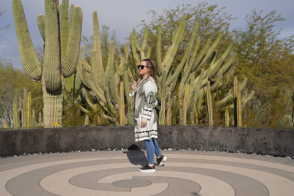 Woman in the gardens posing in front of tall cacti. | Desert Botanical Gardens in Arizona