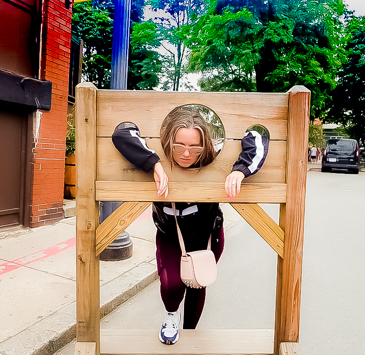 Woman posing in guillotine outside the Witch Dungeon Museum in Salem. | What to do in Salem, MA