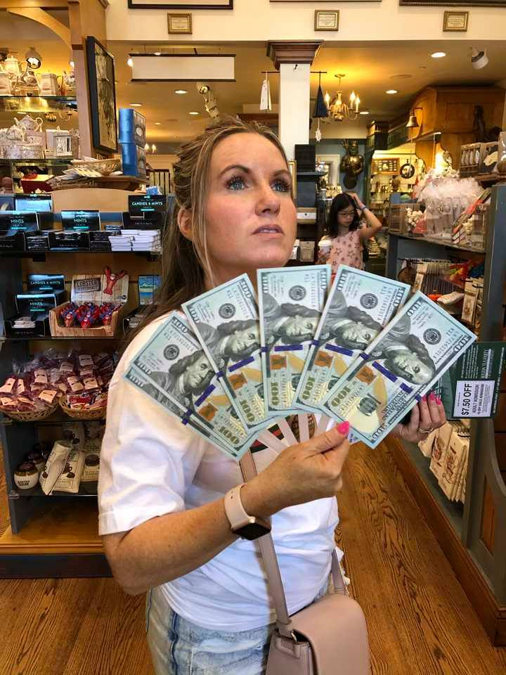 Woman holding fake money in a store in Boston. | Boston, Massachusetts- Adult Getaway
