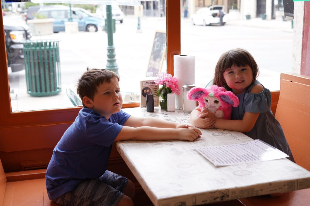Two kids sitting at a restaurant table at the Nutshell Eatery.   A Guide to Granbury, Texas