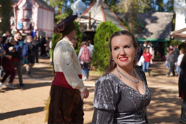 Woman dressed in renaissance clothing with crowds behind her. | Texas Renaissance Festival