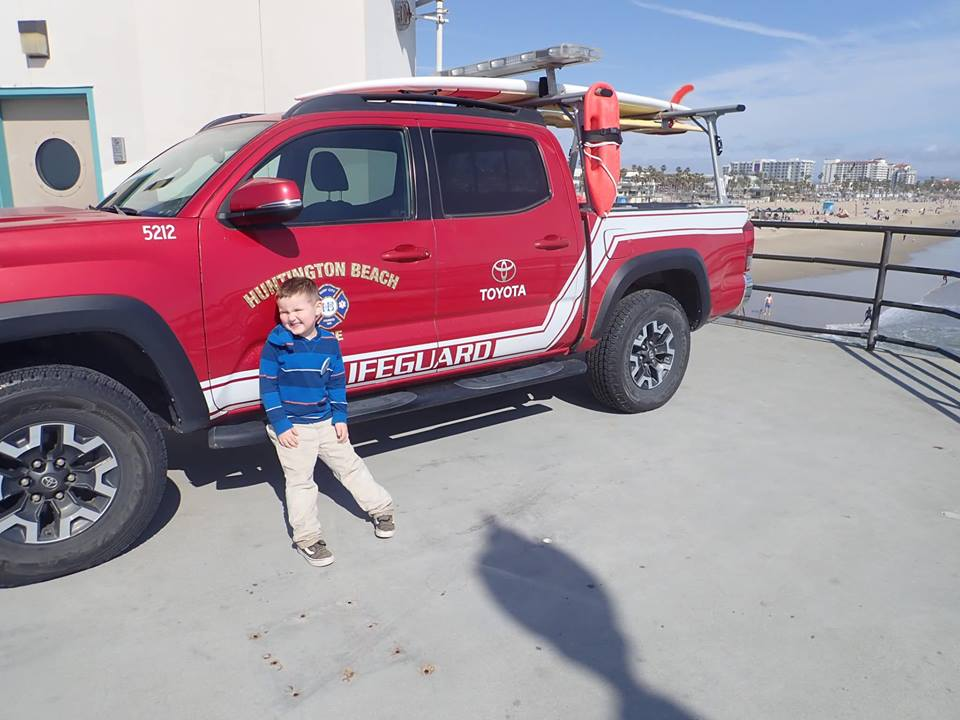 Little boy posing in front of Lifeguard Truck at Huntington Beach Pier in Orange County.| 24 Hours in Orange County, CA