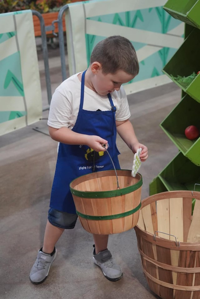 Little boy playing in the pretend farmers market in the animal area at the fair. | State Fair of Texas-Dallas