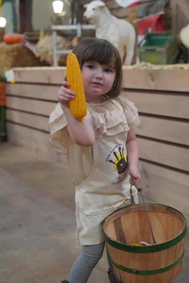 Little girl holding corn on the cobb in the animal area at the fair. | State Fair of Texas-Dallas
