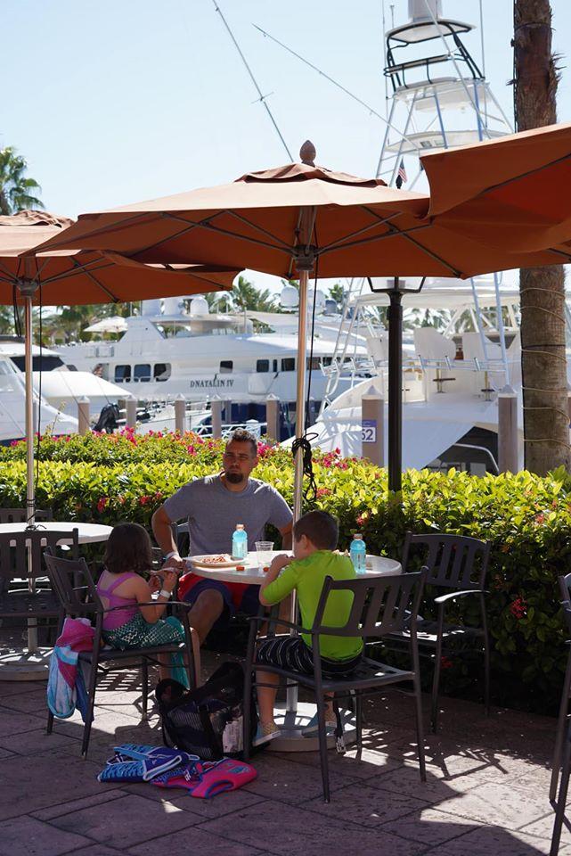 Family sitting at a restaurant table outside eating lunch at the Atlantis resort.   Atlantis, Bahamas