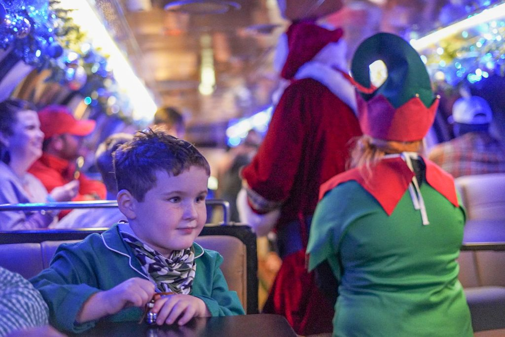 Little boy on the Polar Express Train ride with Santa and an elf blurred in the background.| The Polar Express Train Ride in Palestine, Texas