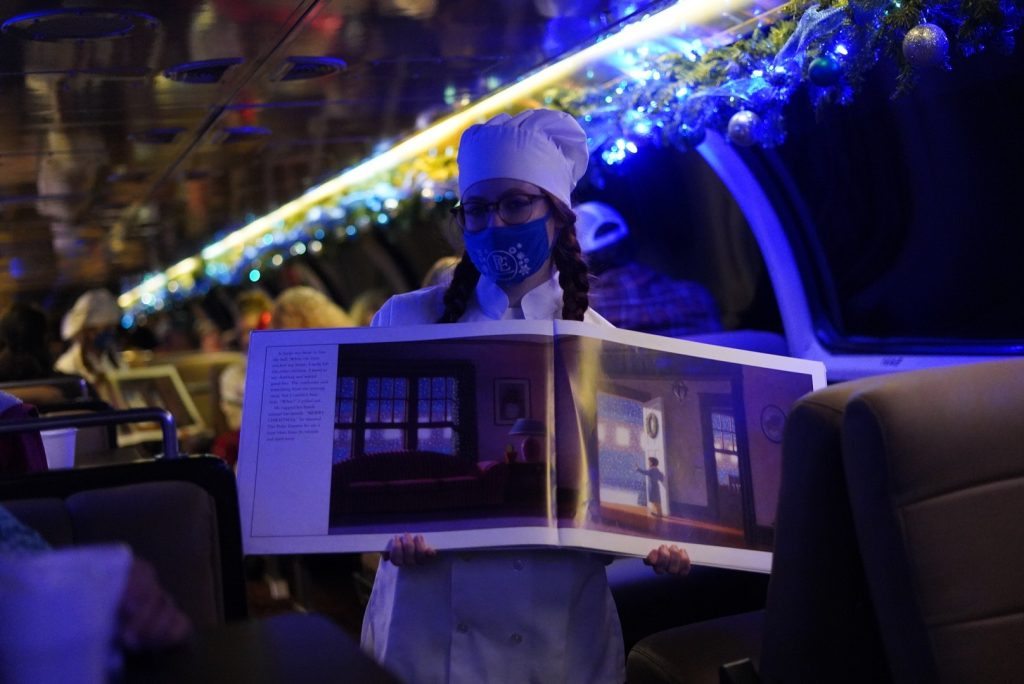 Chef holding an opened Polar Express book in the train. | The Polar Express Train Ride in Palestine, Texas