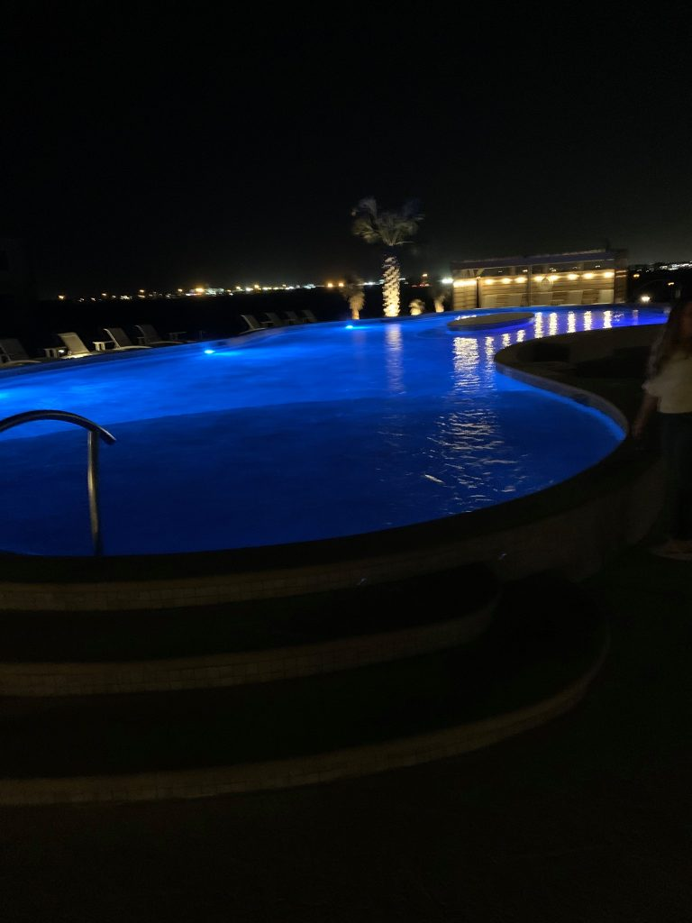 Outdoor pool lit up at night with a blue light. | Lively Beach in Corpus Christi, Texas