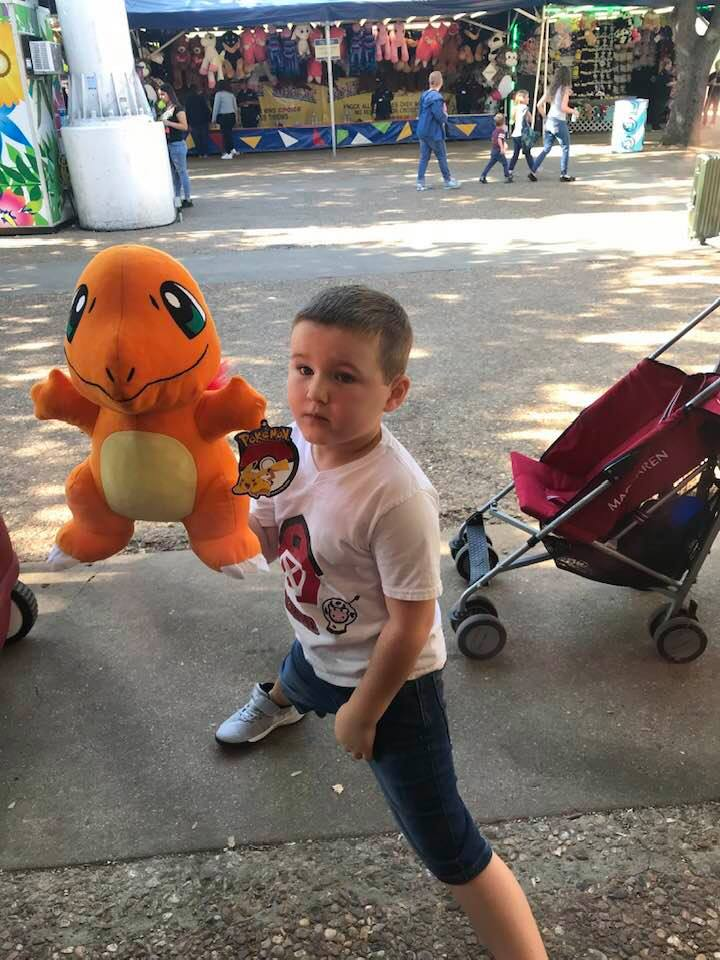 Little boy showing off his prize he won for playing games at the fair. | State Fair of Texas-Dallas