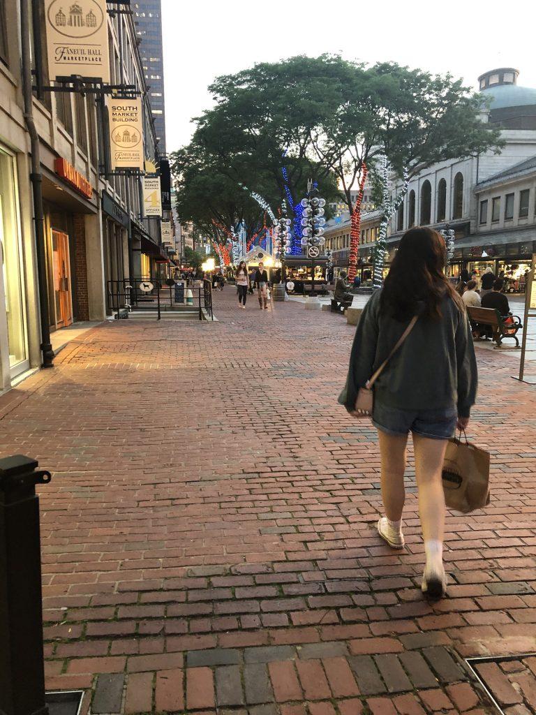Woman walking on street outside Quincy Market in Boston. | Boston, Massachusetts- Adult Getaway