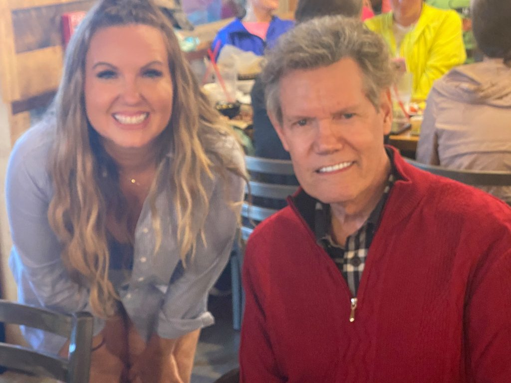 Woman smiling with Randy Travis in restaurant. | Glamping at Silver Spur Resort in Canton, Texas